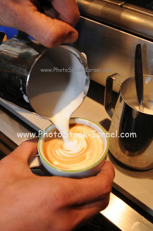 preparing cappuccino Adding hot milk froth to coffee