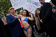 Donald Trump lookalike makes a mock grab with a bikini wearing protester who is holding a placard which reads Dont grab my pussy at the Together Against Trump, national demonstration on 4th June 2019 in London, United Kingdom. Thousands gather in central London to protest against Donald Trumps State Visit to London. Protesters demostrate against his alleged racism, mysogyny, climate denial and interference in British politics.