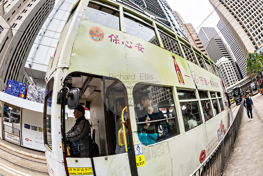 Riders standing on a historic double decker trams traveling in the central district of Hong Kong.