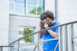 Young man photographing using retro style camera