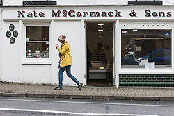 Lady walking past Kate McCormack & Sons butcher shop, Westport, County Mayo, Ireland