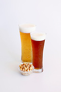 two glass of beer with chickpea snack on white background