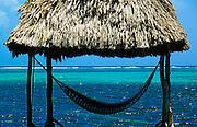 Cabana with hammock overlooking aqua tropical waters, Ambergris Caye, Belize.
