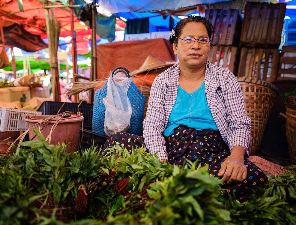 YANGON, MYANMAR - CIRCA DECEMBER 2017: Portrait of woman selling vegetables at street market in Yangon.