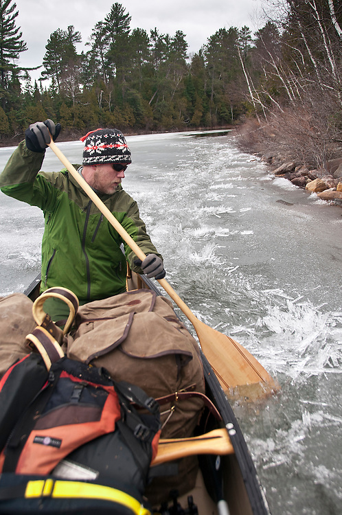 A canoeist smashes through brash ice while paddling during an early spring trip to Lady Evelyn-Smoothwater Provincial Park in Ontario Canada.