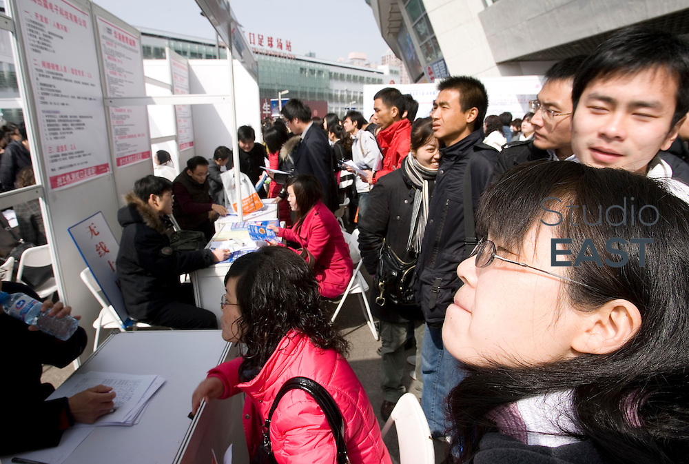 Job-seekers look for job opportunities on billboards at Hong Kou Stadium job fair, Shanghai, China, on February 21, 2009.  A survey conducted by the China Economic Monitoring and Analysis Center predicted that rising unemployment would be the biggest challenge for China's economy this year. Urban unemployment rate, which excludes migrant workers, was estimated to hit 4.6 per cent in 2009, up from 4.2 per cent in the fourth quarter of 2008. China's economy cooled to its slowest pace in seven years in 2008, expanding 9 per cent year-on-year, according to official data. Photo by Lucas Schifres/Pictobank