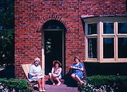 Three women sitting around doorstep of house holding teacups, UK 1963