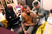 Tattoo artist at work by his stall at the 2nd International Tattoo Convention in London on Saturday, Oct. 7, 2006, in London, UK. With over 15.000 visitors in three days during the 2005 edition, the event placed London in a central position in the tattoo world.  This year about 150 artists ,representing all the tattoo styles, are ticking away with their machines in a very exciting atmosphere. **ITALY OUT**....