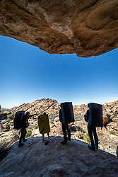 Silhouette of climbers with pads hiking to bouldering site, Hueco Tanks State Park & Historic Site, El Paso, Texas. USA.