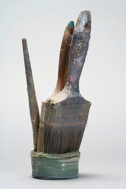 various paint brushes stuck in dried up paint