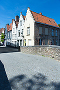 Painted houses with crow-stepped gables - crow steps - in empty street with light and shade in Bruges, Belgium