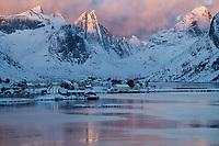 First light shines on winter mountain peaks over Reine and Kirkefjord, Moskenesøy, Lofoten Islands, Norway