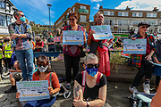 People wearing face protective masks holding pro-refugees and migrants placards are gathered in Market Square, in Dover on Saturday, Sept 5, 2020 - after fears of violence against the refugees announced by far-right groups who are expected to assemble to demonstrate over migrant crossings. Pro-migrant protesters are already gathered in the town on Saturday amid a heavy police presence. Dover MP Natalie Elphicke has urged people to stay away from the protests given the backdrop of the Covid-19 pandemic. British media reports say that on Friday, an activist group projected pro-immigrant messages onto the White Cliffs of Dover ahead of the protests saying 'Rise above fear. Refugees welcome' (VXP Photo/ Vudi Xhymshiti)