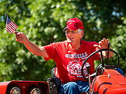 04 JULY 2020 - RUNNELLS, IOWA: A man on a tractor waves the American flag during the 4th of July tractor parade in Runnells, a small community about 25 miles from Des Moines. Most of the Independence Day parades in central Iowa were cancelled because of the COVID-19 (Coronavirus) pandemic. People in Runnells made the decision to go ahead with their parade, the first 4th of July parade in the town in recent memory. Most of the people in the parade were farmers, who drove their tractors through the town.    PHOTO BY JACK KURTZ