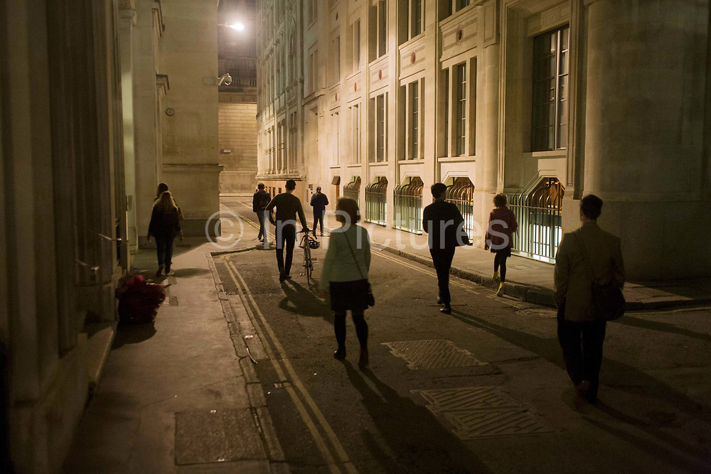 Psychogeographers in the City of London while following the route of the former River Walbrook, walk along Tokenhouse Yard during a walk by the writer Tom Chivers. Emerging from the shadows, and listening to an mp3 audio commentary including water sound effects, poetry and prose by the writer, they individually make their way along towards the Bank of England wall at the far end.