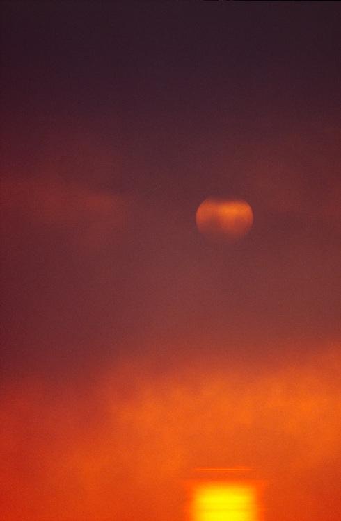 Rising Sun and reflection through fog