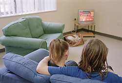 Two residents of homeless hostel sitting together on sofa watching television in shared living room,