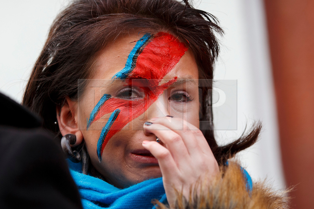 © Licensed to London News Pictures. 11/01/2016. London, UK. A woman dressed as David Bowie paying her respects at his mural in Brixton, where he was born, in south London on Monday, 11 January 2016. Music legend David Bowie died aged 69, after suffering from cancer. Photo credit: Tolga Akmen/LNP