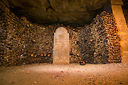 Stacks of bones and skulls in the catacombs of Paris, France.  The catacombs are a vast network of tunnels and tombs below the city.  They were originally built from limestone quarries dating back to the Romans.