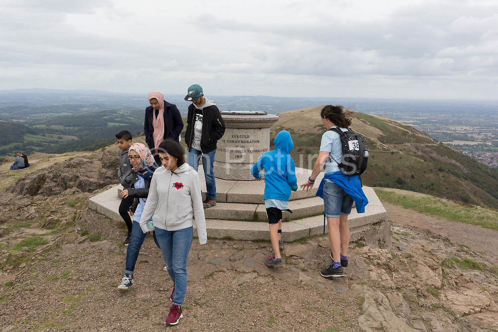 Charity walkers for Help For Heroes reach the summit of the Beacon, on 15th September 2018, in Malvern, Worcestershire, England UK. Worcestershire Beacon, also popularly known as Worcester Beacon, or locally simply as The Beacon, is a hill whose summit at 425 metres 1,394 ft[1] is the highest point of the range of Malvern Hills that runs about 13 kilometres 8.1 mi north-south along the Herefordshire-Worcestershire border, although Worcestershire Beacon itself lies entirely within Worcestershire.