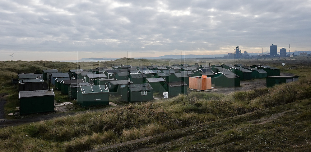 © Licensed to London News Pictures.20/10/15<br /> Redcar, UK. <br /> <br /> Nestled amongst sand dunes the huts of the South Gare Fisherman's Association sit in front of the recently closed SSI UK steel blast furnace in Redcar, England. The closure of the site marks the end of 170 years of steel making heritage on Teesside and was the first of a number of recent closures of steel making plants across the UK.<br /> <br /> Photo credit : Ian Forsyth/LNP