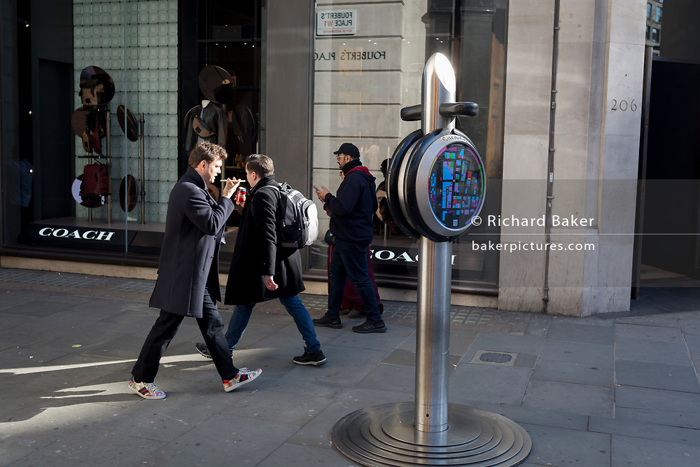 A man speaks into his horizontally-held mobile phone on the corner of Foubert's Place and Regent Street in Westminster, on 26th February, in London, England.