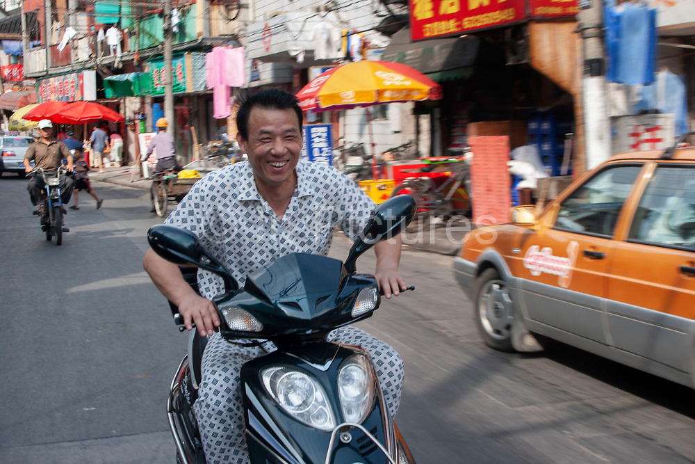 A man wearing pyjamas rides his scooter along Fang Bang Road (Fangbang Lu). This lively street of traditional Chinese housing and street food seems also to be one of the centres of Shanghai's pyjama wearing public. A common sight even in real downtown areas, Pyjamas are worn as a loose, cool, and perhaps fashionable alternative to regular 'daytime' clothes.