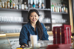 Portrait of a young waitress smiling at coffee shop counter, Freiburg Im Breisgau, Baden-w¸rttemberg, Germany