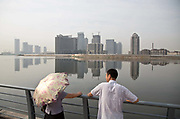 "Locals walk down Tianjin city's own Bund, with a view of the Binhai New Development Zone's Yujiapu and Xiangluowan  districts in Tianjin, China on 16 July 2013. The districts had the ambition of becoming China's newest financial center to rival Shanghai's Pudong, and dubbed by some ""the Manhattan of the East"",  however as the country tries to steer away from an investment driven economy, such projects are facing increasing scrutiny."