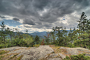 Adirondacks, NY.   Baxter Mountain gave me a fine show on this day, with a sky battle going on.  High pressure was building in, but the storm system refused to give up.  So blue, sunlit sky pushed against storm clouds, and I would be in for a shower soon. On this little open plateau, the view into Keene Valley is a bit obscured, but Dix and it's slides are conveniently featured by the shape of the treeline along the cliffs just beyond the foreground bedrock.  Though I took several exposures for the brighter and darker parts of the sky, I ended up combining two with HDR to hold it together.