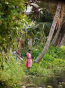 A woman fishes on the banks of the Kerala Backwaters, near Alappuzha, India
