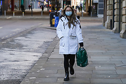 © Licensed to London News Pictures. 05/01/2021. Manchester, UK. A shopper wearing a face mask  walks in a near deserted street in central Manchester as England entered a seven-week national lockdown from Tuesday, January 5, until the end of the February half term .  Photo credit: Ioannis Alexopoulos/LNP