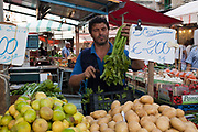 A market trader cleans celery on his stall in the Capo Market, Palermo, Italy