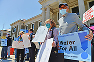 """Mineola, New York, USA. April 26, 2021. Activists hold signs saying STOP TAXING OUR WATER, and Food and Water Watch signs: Water for ALL!"""" Faced with a 26% rate increase from New York American Water going into effect May 1, 2021, activists and residents who are NYAW customers rally to urge NYS Assemby to push through legislation, before that date, corresponding with NYS Senate Bill S989A to establish a Nassau County Water Authority and except water works corporations in counties of populations over one million from a special franchise tax."""