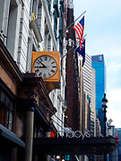 R H Macy department store original and modern shop signs plus clock and flags on the exterior of the famous store in New York City.
