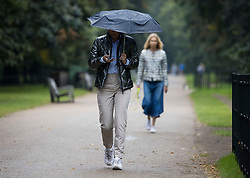 © Licensed to London News Pictures. 31/08/2021. London, UK. A woman shelters from the rain, underneath an umbrella in Hyde Park, London, on a damp and grey day. Today, August 31st, is the last day of meteorological summer. Photo credit: Ben Cawthra/LNP