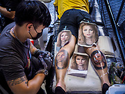28 OCTOBER 2018 - BANGKOK, THAILAND: A man gets his legs tattooed at the 2018 MBK Center Tattoo Fest. Tatoo artists from around the world came to participate in the festival, which featured both modern (using tattoo machines) and traditional methods (done by hand with long needles) of tattooing.     PHOTO BY JACK KURTZ