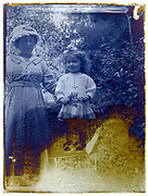 mother posing with toddler girl  child early 1900s eroding glass plate photo