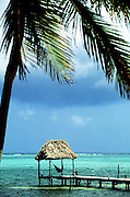 Cabana with hammock overlooking aqua tropical waters at the end of a dock, Ambergris Caye, Belize