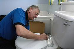 Housing Association plumber fitting toilet seat UK