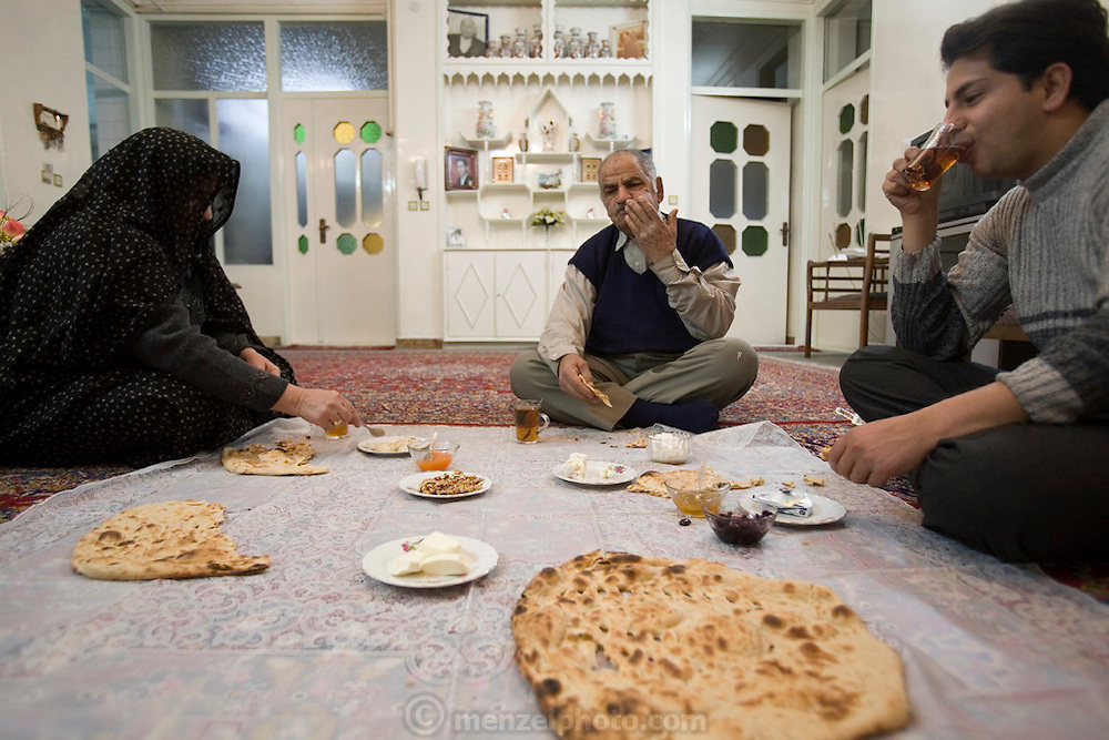 Mohammed Riahi*, and his father and mother at breakfast on the floor of their spacious home in Yazd, Iran. Mohammed, 30, lives at home with his parents until he marries. Parents are Amin Riahi, 72, and Fakhri Ghanad, 60. *Mohammed is one of the 101 people selected for inclusion in Peter Menzel & Faith D'Aluisio's upcoming book Nutrition 101 (2008) about what people around the world eat in one day's time.