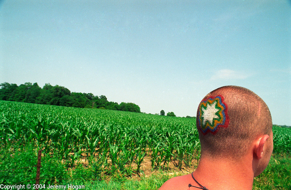 Copyright ©Ê2004 Jeremy Hogan - All Rights Reserved..A deadhead walking past cornfield Grateful Dead show at Deercreek, Indiana during July 1995 has a psychadelic design on the back of his head. ..Generation x, genx, grateful dead, deadhead, deadheads, dropout, hippy, hipster, hip, traveler, youth culture, journey, Americana, 90s, 1990s, counterculture, walking, mystery, mysterious, colorful.