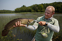 Angler and guide Drew Price displays a fly caught bowfin on lake champlain
