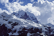 """Trek to see Siula Grande (east face, 20,800 feet or 6344 meters elevation) and other spectacular peaks in the Cordillera Huayhuash, Andes Mountains, Peru, South America. Siula Grande was the subject of the gripping 2003 British docudrama """"Touching the Void."""" In 1985, climbers Joe Simpson and Simon Yates scaled the treacherous Siula Grande, one of the last unconquered mountains in the Andes, but after Joe broke his leg, their descent became one of the most amazing survival stories in mountaineering history. This photo shows the northeast face, but they climbed Siula Grande from a valley on the other side (the west face) and descended along the north ridge, on the upper right. The 2003 movie is based upon Joe Simpson's harrowing book, """"Touching the Void: The True Story of One Man's Miraculous Survival."""""""