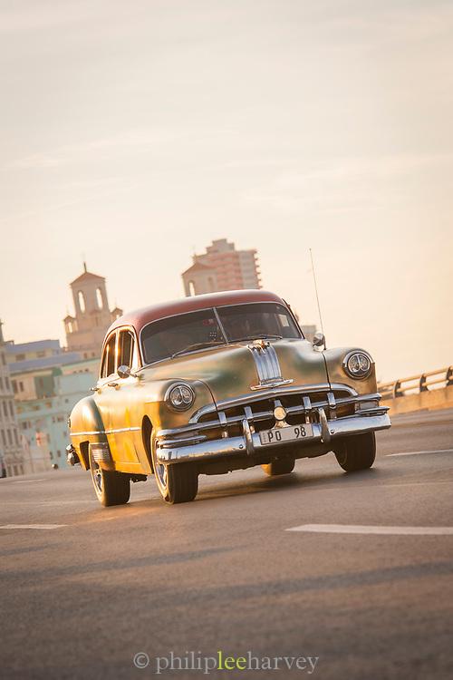 Vintage car driving along Malecon road at sunset, Havana, Cuba