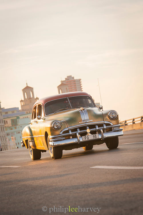 Vintage car driving along Malecon road at sunset, Havana, Cuba