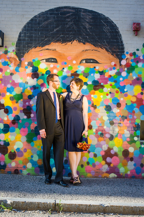 A bride and groom with a mural in downtown Waltham, MA.