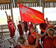 A group of monks celebrates on a teak bridge in U Bein the eleectoral victory. Myanmar, 2012.