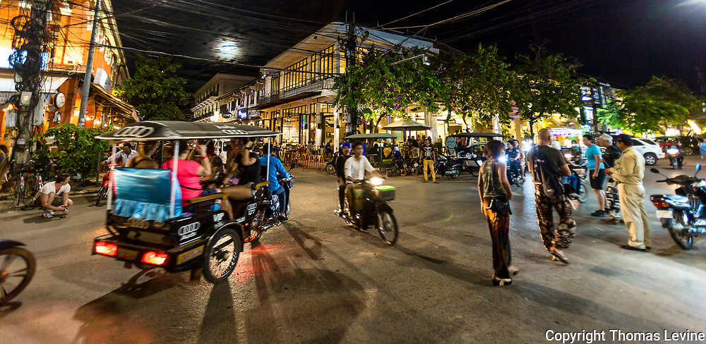 Night time on the streets in Siem Reap with busy traffic and people walking. (Not on Pub street) (people not recognizable in motion) small amount of noise)