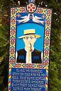 Tombstone showing a man in traditional clothes, The  Merry Cemetery ( Cimitirul Vesel ),  Săpânţa, Maramares, Northern Transylvania, Romania.  The naive folk art style of the tombstones created by woodcarver  Stan Ioan Pătraş (1909 - 1977) who created in his lifetime over 700 colourfully painted wooden tombstones with small relief portrait carvings of the deceased or with scenes depicting them at work or play or surprisingly showing the violent accident that killed them. Each tombstone has an inscription about the person, sometimes a light hearted  limerick in Romanian. .<br /> <br /> Visit our ROMANIA HISTORIC PLACXES PHOTO COLLECTIONS for more photos to download or buy as wall art prints https://funkystock.photoshelter.com/gallery-collection/Pictures-Images-of-Romania-Photos-of-Romanian-Historic-Landmark-Sites/C00001TITiQwAdS8